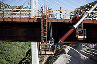Scill, Italy - 18 July, 2012:  Worker on the Favazzina bridge on 18 July, 2012, in Scilla, Italy. The Autostrada A3 Salerno-Reggio Calabria is a motorway in the south of Italy, which runs from Salerno to Reggio Calabria via Salerno. Due to its notorious poor conditions of maintenance, and its difficult route, the motorway has been often taken as a symbol of the backwardness and economical problems of southern Italy.