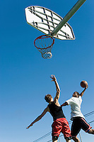 Basketball player guarding another as he tries to shoot basketball low angle view