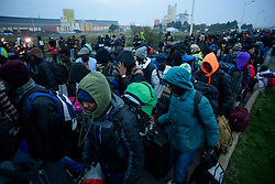 © Licensed to London News Pictures. 24/10/2016. Calais, France. Thousand of migrant queue to board busses as the evacuation and demolition begins at the migrant camp in Calais, known as the 'Jungle'. French authorities have given an eviction order to thousands of refugees and migrants living at the makeshift living area of the French coast. Photo credit: Ben Cawthra/LNP