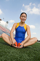 Female athlete stretching, portrait