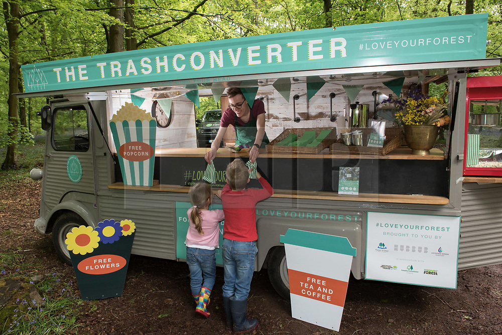 """© Licensed to London News Pictures. <br /> **EMBARGOED UNTIL 00.01am MONDAY 15 MAY, 2017**. Forest of Dean, Gloucestershire, UK. """"Please don't leaf it behind!"""" George and Grace Bell hand in rubbish collected in the Forest of Dean to the Trash Converters van that gives out free drinks and snacks in exchange for rubbish that people find and bring to convert. The scheme is part of a new behaviour change campaign by Hubbub to tackle the rural litter epidemic. www.hubbub.org.uk/trashconverter. Trash Converters launch in the Forest of Dean, with a display of flowers created from waste, and with a van that gives out free drinks and snacks in exchange for rubbish that people find and bring to convert. For further details about the launch on 15 May please contact:<br /> Rachel Parkes0777 565 2919 / rachel.parkes@greenhousepr.co.uk<br /> Helen Bell07880 560 233 / helen.bell@greenhousepr.co.uk <br /> Picture credit : Simon Chapman/LNP"""