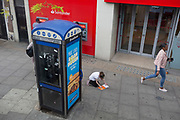 Next to a phone kiosk, a girl kneels on the pavement with a colouring book on the Walworth Road in Southwark, on 30th May 2019, in London, England.