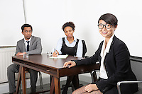Portrait of Asian female with multiethnic colleagues in background at desk in office