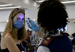Rosemary Arends, an assistant nurse-flight attendant, checks the temperature of passenger Paula Brooks, part of group of South African nationals at Miami International Airport boarding a special charter flight by South African Airways. Amid the coronavirus pandemic, the flight will repatriate more than 300 South African workers who were supposed to spend these months working at South Florida hotels and resorts, on Tuesday, April 14, 2020. Photo by Pedro Portal/Miami Herald/TNS/ABACAPRESS.COM