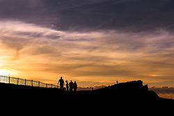 Holidaymakers seen in silhouette as a spectacular sunset breaks over Porth Island in Newquay.