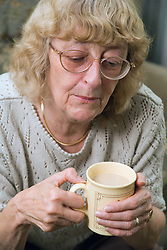Woman looking serious and holding a mug of coffee,