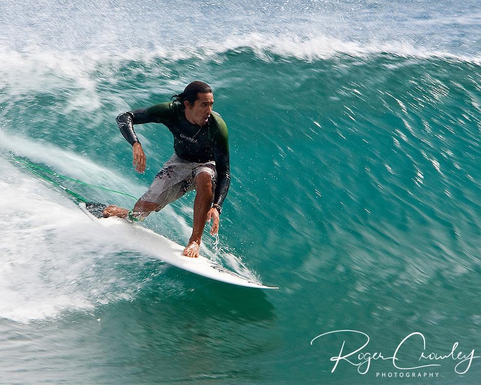 A surfer on Shipwreck Beach Kaua'i Hawaii rides a small wave.