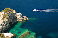 A speedboat passing limestone cliffs on the south coast of Paxos, Ionian Islands, Greece