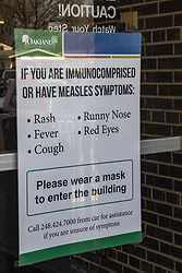 March 27, 2019 - Southfield, Michigan, U.S. - A sign on the door of the Oakland County Health Department asks anyone with measles symptoms to wear a mash before entering the building. The health department is urging vaccinations since 22 measles cases were confirmed in the area following the visit of an infected traveler from Israel. (Credit Image: © Jim West/ZUMA Wire)