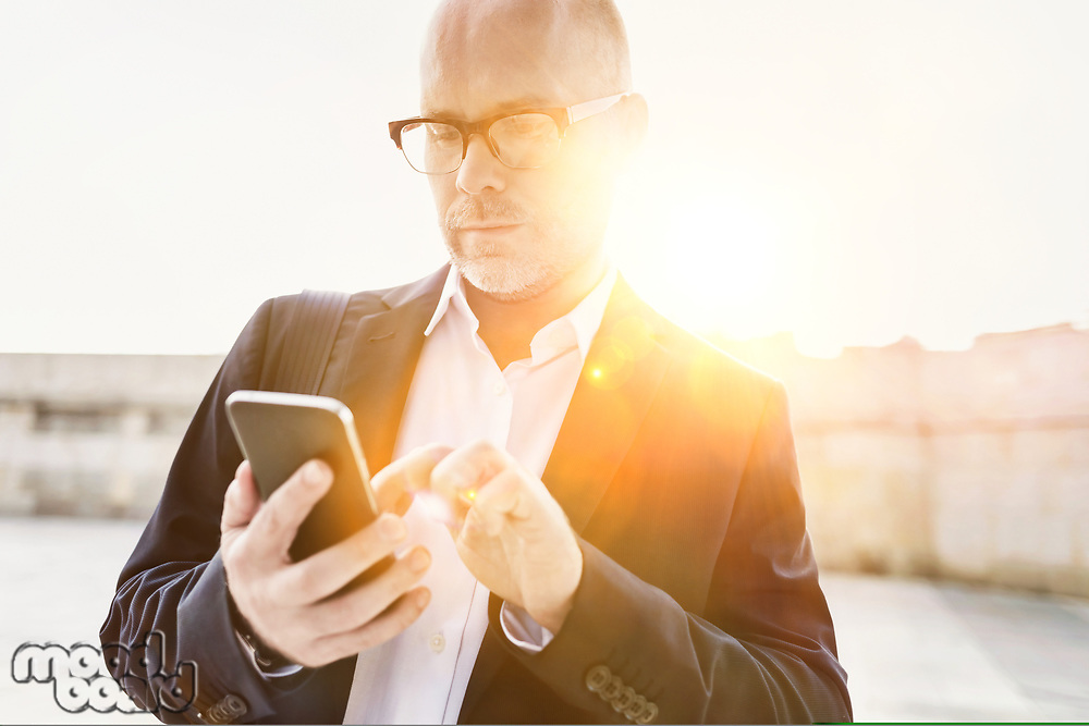 Portrait of businessman using smartphone while leaning on wall