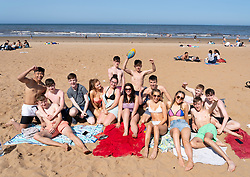 Portobello,Scotland, UK. 28 June, 2019. Warm temperatures and unbroken sunshine brought hundreds of people and families to this famous beach outside Edinburgh. Pictured, Group of young people enjoying the sun.