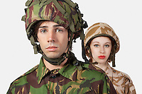 Portrait of young man and woman in military clothes against gray background