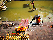 04 MARCH 2017 - KATHMANDU, NEPAL:  A man cleans the ghat used to wash the body of deceased at the ghats on the banks of the Bagmati River at Pashupatinath, a complex of important Hindu temples in Kathmandu. The Bagmati River runs through the complex. It is Nepal's most holy river, and this stretch of the river is like Varanasi in India. The river bank is lined with cremation ghats. Many Hindus, from both Nepal and India, make pilgrimages to Pashupatinath.   PHOTO BY JACK KURTZ