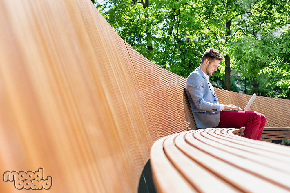 Young attractive businessman working on his laptop while sitting on bench