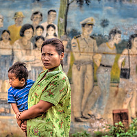 Mother carries child past warning sign in Snuol, Cambodia