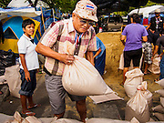 """30 DECEMBER 2013 - BANGKOK, THAILAND: Anti-government protestors fortify their positions by placing sandbags across Ratchadamnoen Road in Bangkok. Violence around the anti-government protest sites has escalated in recent days and several protestors have been hurt by small explosive devices thrown at their guard posts. As a result, protestors are fortifying their positions with sandbags and bunkers. Suthep Thaugsuban, the leader of the anti-government protests in Bangkok, has called for a new series of massive protests after the 1st of the year and said it the shutdown, or what he described was the seizure of the capital, would be the day when """"People's Revolution"""" would """"begin to end and uproot the Thaksin regime.""""          PHOTO BY JACK KURTZ"""