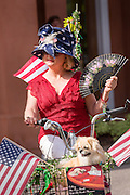 A woman and her dog ride a tricycle decorated in red, white and blue during the I'On neighborhood Independence Day parade July 4, 2015 in Mt Pleasant, South Carolina.