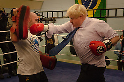 North Woolwich, London, October 28th 2014.  The Mayor of London, Boris Johnson, visits a training session at Fight for Peace Academy in Newham.<br /> <br /> Fight for Peace uses boxing and martial arts combined with education and personal development to realise the potential of young people in the borough at risk of crime and violence. First established in Rio in 2000 by Luke Dowdney MBE, it was replicated in Newham in 2007. It is now expanding globally and began rolling out across the UK.<br /> Pictured: Mayor Boris Johnson spars in the ring with one of the Fight For Peace trainers.