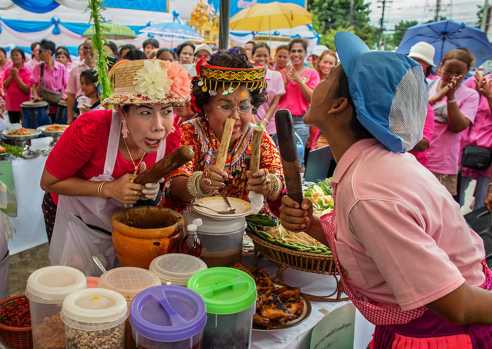 Thai women enjoy the music and festivities as Rural Thailand celebrates HM Queen Sirikit's birthday. Winning contestants are chosen by the flavor of the food and for how well they entertain the crowd.