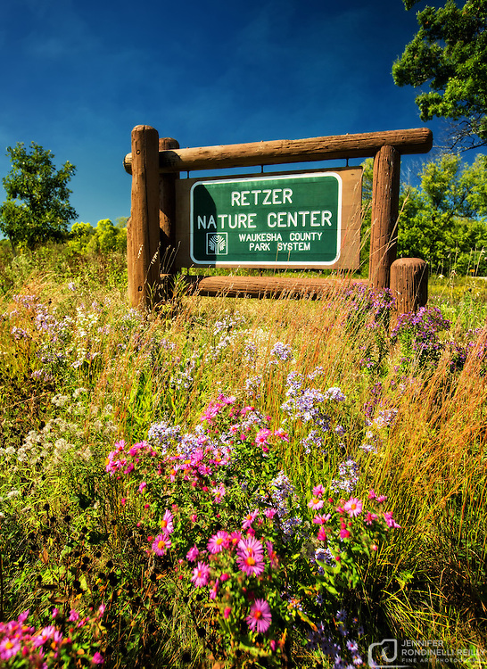 Retzer Nature Center entrance sign in a field of flowers.
