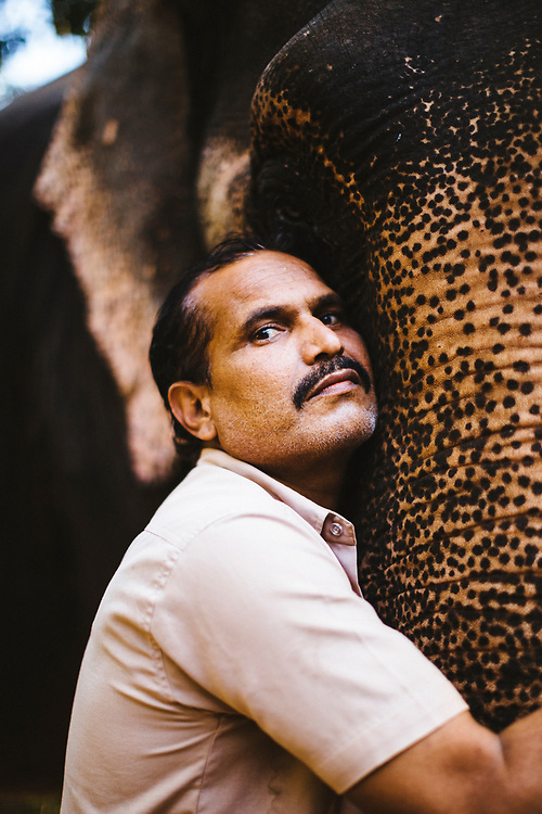 A trainer poses for a portrait with his elephant at the Tropical Spice Plantation in Goa, India.