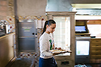"NAPLES, ITALY - 8 DECEMBER 2017: A waitress carries a pizza here at Pizzeria Gino Sorbillo in Naples, Italy, on December 8th 2017.<br /> <br /> On Thursday December 7th 2017, UNESCO added the art of Neapolitan ""Pizzaiuolo"" to its list of Intangible Cultural Heritage of Humanity.<br /> <br /> The art of the Neapolitan 'Pizzaiuolo' is a culinary practice comprising four different phases relating to the preparation of the dough and its baking in a wood-fired oven, involving a rotatory movement by the baker. The element originates in Naples, the capital of the Campania Region, where about 3,000 Pizzaiuoli now live and perform. Pizzaiuoli are a living link for the communities concerned. There are three primary categories of bearers – the Master Pizzaiuolo, the Pizzaiuolo and the baker – as well as the families in Naples who reproduce the art in their own homes. The element fosters social gatherings and intergenerational exchange, and assumes a character of the spectacular, with the Pizzaiuolo at the centre of their 'bottega' sharing their art.<br /> <br /> In Naples, pizza makers celebrated the victory by giving away free pizzas."
