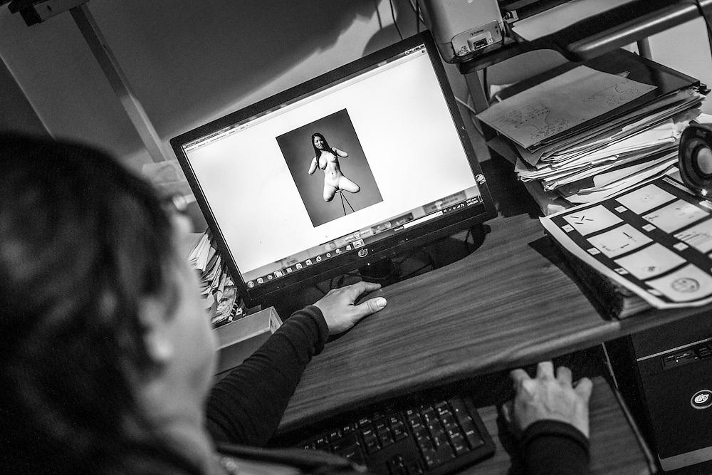 """Carolina Mora observa una fotografía de una mujer con amputaciones en su consultorio. Mora es una psicólogo clínico que estudia a los """"Devotee"""", aquellas personas que sienten deseo sexual o tienen preferencia sexual por alguien con discapacidad física. Caracas, 13 de junio de 2014. (Foto/Ivan Gonzalez)"""