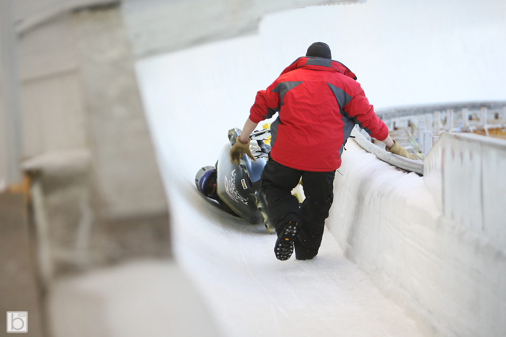 A track worker rushed to assist the two-man bobsled driven by Phil Parsons former NASCAR driver and current SPEED Channel commentator slides through curve 19 at the Olympic Sports Complex in Lake Placid, N.Y. after crashing in curve 19 during a training run at the second annual Bodine Bobsled Challenge in Lake Placid, N.Y., Jan 4-6 2007.  NASCAR, BUSCH and NHRA drivers and personalities attended the event to benefit the Bo-Dyn Bobsled Project which was founded by Geoff Bodine to develop and produce competitive bobsled designs for the United States Bobsled Team.  Parsons was not injured in the accident.<br />
