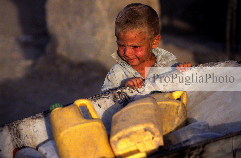 Young boy trasporting water