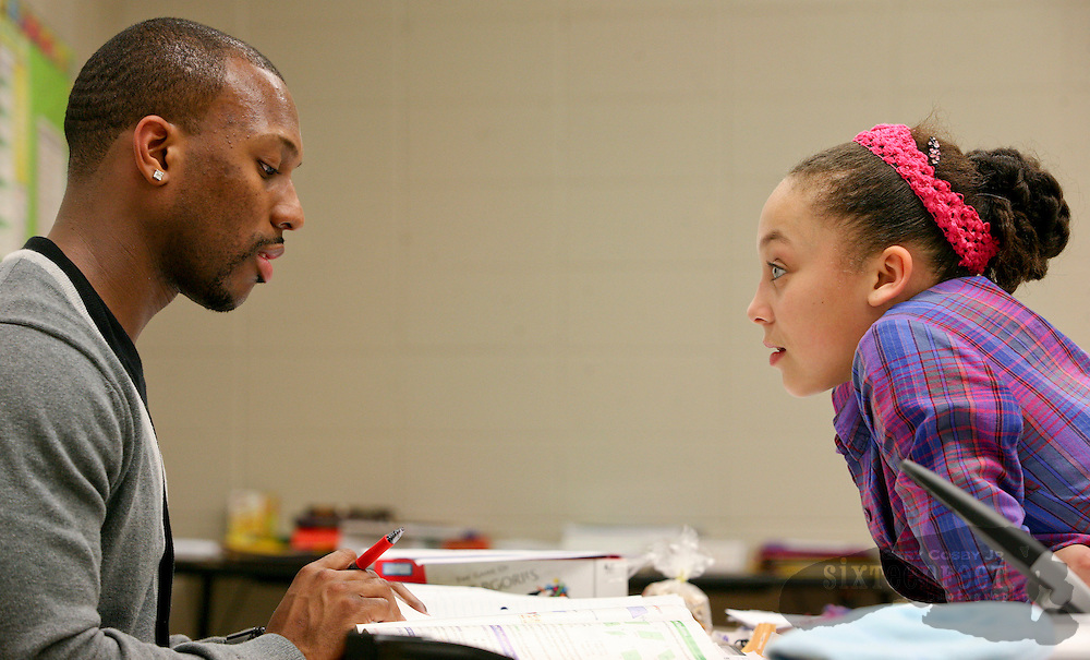 Photo by Gary Cosby Jr.   Ramzee Robinson works with children at Butler High School in the Huntsville Inner-City Learning Center Tuesday, February 21, 2012 in Huntsville, Alabama.  Aazhenii Nye pays attention to Robinson as he helps her with her homework. Robinson is a new member of the Denver Broncos.
