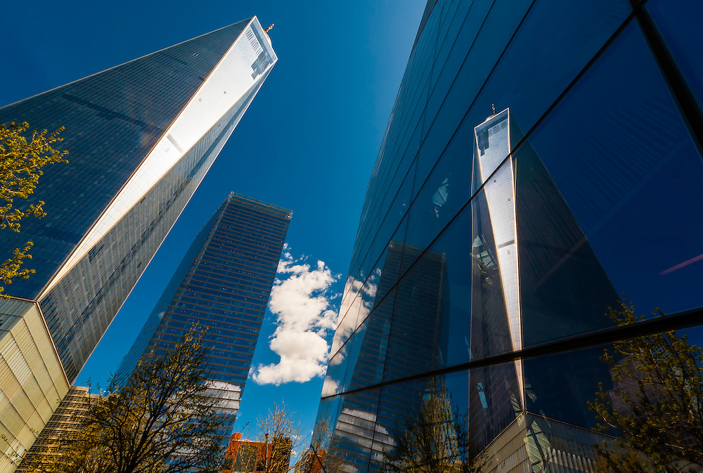 National September 11 Memorial & Museum (on right) with the new One World Trade Center (left) reflected on it, New York, New York USA.