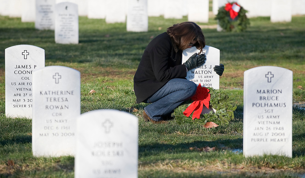 Sarah Walton hugs her late husband's gravestone after leaving a holiday wreath for him in Arlington National Cemetery, in Arlington, Virginia, USA on 12 December 2009. Family members and scores of volunteers placed 15,000 balsam fir wreaths, which are donated by the Worcester Wreath Company of Harrington, Maine, in an annual event to honor the dead and mark the winter holiday season.