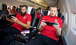 CARDIFF, WALES - Monday, September 4, 2017: Wales' Joe Ledley, Gareth Bale and goalkeeper Wayne Hennessey play Mario Kart on the Nintendo Switch on the team plane as the squad depart Cardiff Airport to travel to Chișinău ahead of the 2018 FIFA World Cup Qualifying Group D match against Moldova. (Pic by David Rawcliffe/Propaganda)