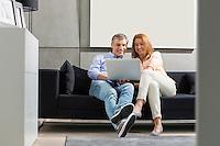Full-length of smiling couple using laptop on sofa