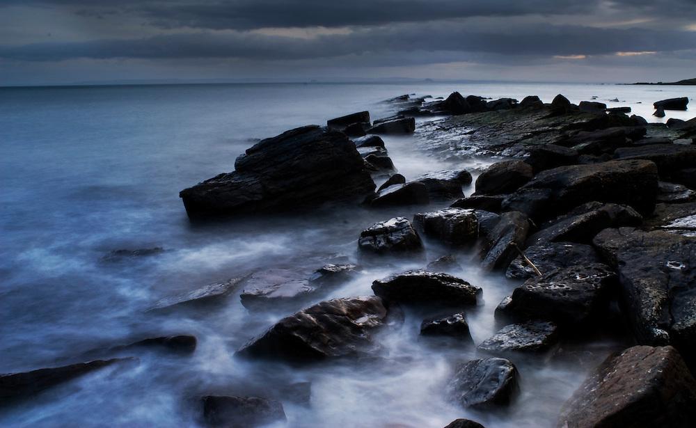 A long exposure of the sea swirling around rocks at twilight, the Fife coastline, Scotland.