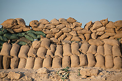 © Licensed to London News Pictures. 02/09/2015. Bashiqa, Iraq. A sandbagged Kurdish peshmerga defensive position on Bashiqa Mountain, Iraq.<br /> <br /> Bashiqa Mountain, towering over the town of the same name, is now a heavily fortified front line. Kurdish peshmerga, having withdrawn to the mountain after the August 2014 ISIS offensive, now watch over Islamic State held territory from their sandbagged high-ground positions. Regular exchanges of fire take place between the Kurds and the Islamic militants with the occupied Iraqi city of Mosul forming the backdrop.<br /> <br /> The town of Bashiqa, a formerly mixed town that had a population of Yazidi, Kurd, Arab and Shabak, now lies empty apart from insurgents. Along with several other urban sprawls the town forms one of the gateways to Iraq's second largest city that will need to be dealt with should the Kurds be called to advance on Mosul. Photo credit: Matt Cetti-Roberts/LNP