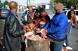 Cape Town-180829 Street vendors cutting the hair of Smiley using the pair of garden scissors. The Sheep head also know as Smiley is very popular in the township it used to be cooked only if threr was traditional cremony nowadays there are many places that clean and sell this delicacy,cooked or uncooked  Pictures Ayanda Ndamane/African/news/agency ANA