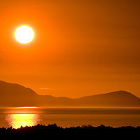 The recent spell of hot weather has brought about some spectacular sunsets. This picture of the sun setting over the north end of Arran was taken from a hill behind Ayr using a 300mm lens. People should always remember never to look directly at the sun through a camera lens and use dark glasses so no damage is done to the eyes. The sun is still powerful, even when almost below the horizon.