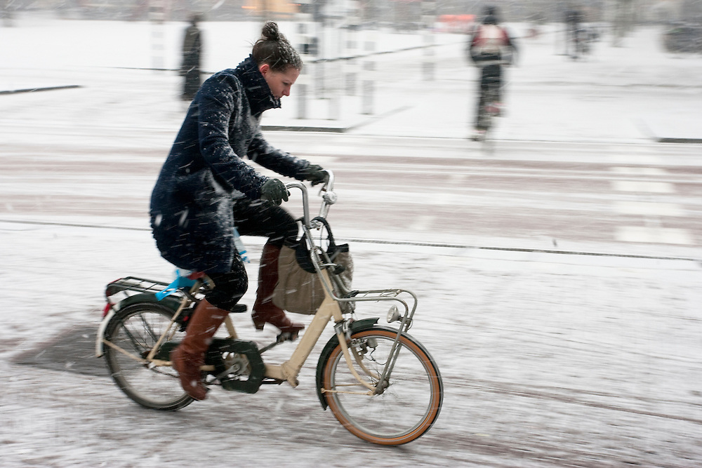 Een vrouw fietst op een vouwfiets door de sneeuw in Utrecht