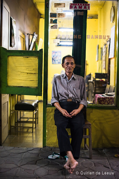 Barber sitting in front of his old fashion barbershop located in central Surakarta, Java.