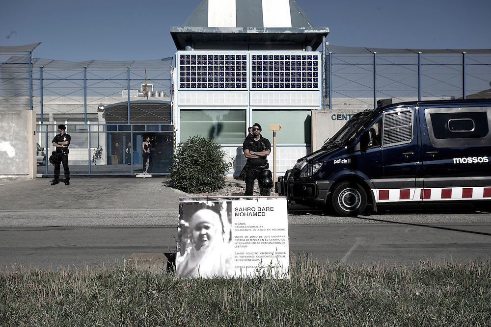 The Mossos d'Esquadra - the police force of Catalonia, stand  by the entrance of the CIE with in front, <br /> a cartel denouncing the death of Sahro Bare Mohamed who died while being under custody in the CIE of Leersum - Netherlands - in June 2010.  She repeatedly requested medical attention and was denied it even if she was pregnant. Protest organized by &quot;Tancarem el CIE&quot; - Barcelona  20/06/2015