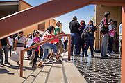 """25 AUGUST 2012 - PHOENIX, AZ:  People wait in line to be let into the deferred action workshop Saturday morning. The line snaked through the parking lot. Hundreds of people lined up at Central High School in Phoenix to complete their paperwork to apply for """"Deferred Action"""" status under the Deferred Action for Childhood Arrivals (DACA) program announced by President Obama in June. Volunteers and lawyers specialized in immigration law helped the immigrants complete the required paperwork. Under the program, the children of undocumented immigrants brought to the US before they turned 16 years old would not be subject to deportation if they meet a predetermined set of conditions.    PHOTO BY JACK KURTZ"""