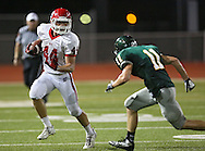 Washington's Connor Vincent (44) eyes Kennedy's Jacob Shannon (11) on a run during their game at Kinston Stadium in Cedar Rapids on Friday, August 30, 2013.