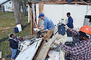 Volunteers help clean houses affected by Sunday's EF4 tornado on Saturday morning.