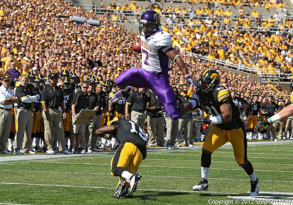 September 15 2012: Northern Iowa Panthers running back David Johnson (7) jumps over Iowa Hawkeyes defensive back B.J. Lowery (19) as he is grabbed by Iowa Hawkeyes linebacker Anthony Hitchens (31) during the first quarter of the NCAA football game between the Northern Iowa Panthers and the Iowa Hawkeyes at Kinnick Stadium in Iowa City, Iowa on Saturday September 15, 2012. Iowa defeated Northern Iowa 27-16.