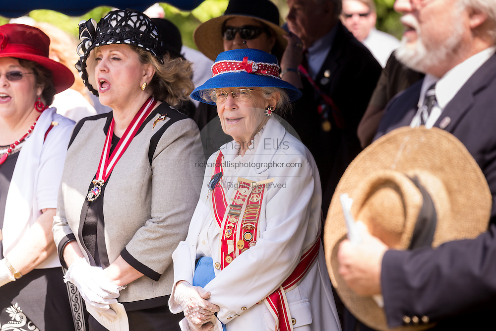 """President General of the United Daughters of the Confederacy June Murray Wells and Director of the Confederate Museum sings """"Dixie"""" during Confederate Memorial Day at Magnolia Cemetery April 10, 2014 in Charleston, SC. Wells traces here heritage back 345 years to the first settlers in Charleston."""