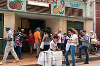 People waiting in line at a bodega, during lunchtime in Havana.
