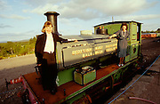Passengers of the Royal Scotsman take a souvenir photo with an old steam engine at the railway museum at Boat of Garten.
