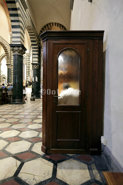 person in a confessional during mass Italy