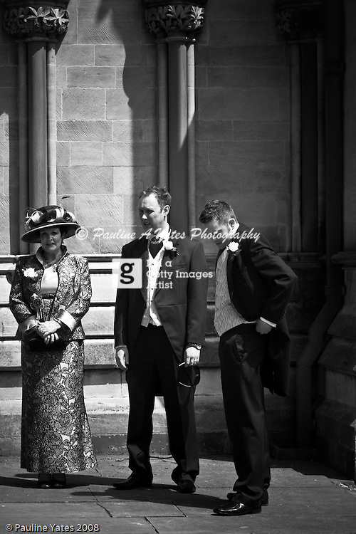 A last minute adjustment to the Best Man as the groom and his mum wait in the sun.